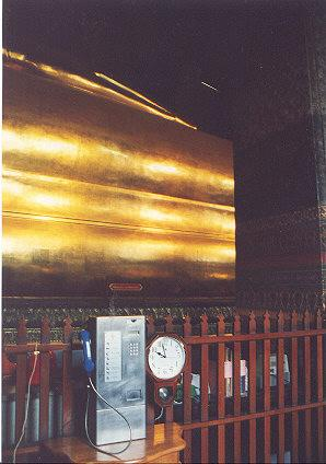 "In a temple.  The golden figure is the Reclining Buddha, a bronze stature 70 feet long.  It was unusual to find a phone near a religious symbol as well as in a sacred temple.  It took coins.</BR></BR><span class=""date-display-single"" property=""dc:date"" datatype=""xsd:dateTime"" content=""1996-11-26T00:00:00+00:00"">Nov 26, 1996</span>"