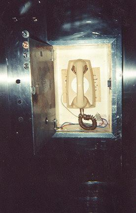 "An emergency phone in a lift.  Lots of exposed wires.  Lifiting the handset give a dial-tone then the sound of pulse dialling.</BR></BR><span class=""date-display-single"" property=""dc:date"" datatype=""xsd:dateTime"" content=""1995-11-02T00:00:00+00:00"">Nov 02, 1995</span>"